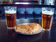 Dos vasos de cerveza con los soplos tallados en la tabla de un diablo foto de archivo libre de regalías
