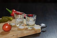 Dos vasos de medida de vodka en la tabla de cortar imágenes de archivo libres de regalías