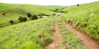 Dos vehículos que viajan en pista de tierra en montañas Imágenes de archivo libres de regalías