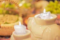 Dos velas ardientes en un fondo borroso de uvas verdes Imagen de archivo libre de regalías