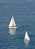 Dos velas blancas en el agua azul Fotos de archivo