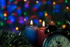 Dos velas con el reloj y la Navidad juegan con las luces multicoloras en fondo Foto de archivo