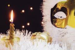 Dos velas con el reloj y los regalos de la Navidad con las luces multicoloras en fondo Imagenes de archivo