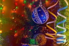 Dos velas con el reloj y los regalos de la Navidad con las luces multicoloras en fondo colorean pendiente Imagenes de archivo