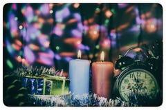 Dos velas con el reloj y los regalos de la Navidad con las luces multicoloras en vieja imagen retra del fondo Foto de archivo libre de regalías