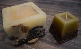 Dos velas con los ornamentos naturales en un fondo de madera de los granos de café Imagen de archivo