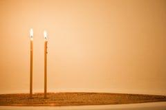 Dos velas en arena fotografía de archivo