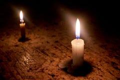 Dos velas en línea rematan la tabla de piedra Foto de archivo