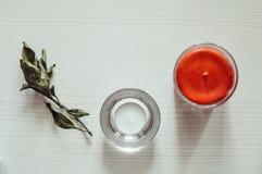 Dos velas que se colocan en un fondo de madera blanco fotos de archivo