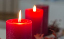 Dos velas rojas del advenimiento están enterrando brillantemente en una guirnalda moderna del advenimiento Fotos de archivo