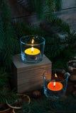 Dos velas y decoraciones ligeras de la Navidad y del Año Nuevo Fotos de archivo libres de regalías