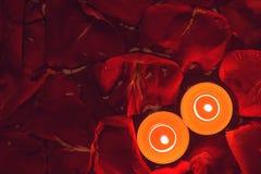 Dos velas y fondo de los pétalos color de rosa Fotografía de archivo