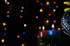 Dos velas y Navidades juegan con las luces multicoloras en fondo Imagen de archivo libre de regalías
