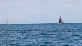 Dos veleros en el lago Michigan uno debajo de la vela el otro viajar en automóvili almacen de metraje de vídeo