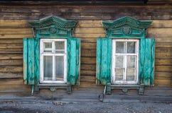 Dos ventanas con el arquitrabe tallado de madera en la casa de madera vieja en la ciudad rusa vieja Foto de archivo libre de regalías