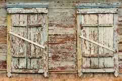 Dos ventanas de madera viejas con los obturadores cerrados Fotos de archivo