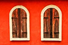 Dos ventanas de madera viejas en la pared roja Fotos de archivo