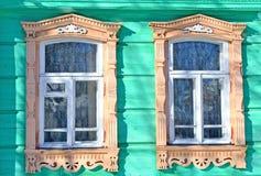 Dos ventanas en la pared de una casa de madera en el estilo ruso Fotos de archivo libres de regalías