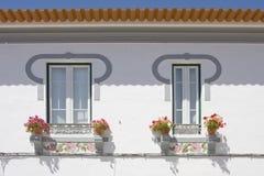 Dos ventanas en un fondo blanco de la pared en Algarve Imágenes de archivo libres de regalías
