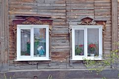 Dos ventanas en una casa de madera vieja adornada con la talla de madera Foto de archivo