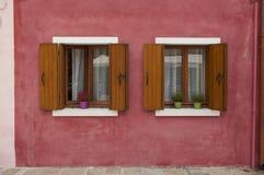 Dos ventanas en una pared roja de una casa colorida de la isla de Burano Fotografía de archivo libre de regalías
