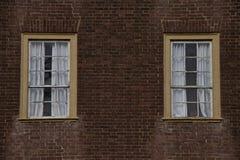 Dos ventanas rectangulares en la pared de ladrillo roja Imagen de archivo libre de regalías