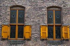 Dos ventanas viejas con las barras de hierro y los obturadores de madera Fotos de archivo libres de regalías