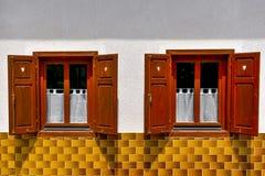 Dos ventanas viejas con los obturadores abiertos en la pared blanca y el ti amarillo Imágenes de archivo libres de regalías