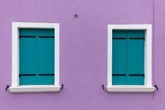 Dos ventanas viejas con los obturadores azules claros en la pared violada clara Foto de archivo libre de regalías