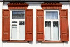 Dos ventanas con los obturadores rojos de madera Imágenes de archivo libres de regalías