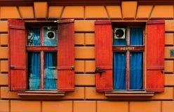 Dos ventanas viejas con los obturadores rojos en la pared de piedra con las cortinas azules Fotografía de archivo