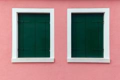 Dos ventanas viejas con los obturadores verde oscuro en la pared rosa clara Fotografía de archivo libre de regalías