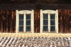Dos ventanas viejas en casa de madera Imagenes de archivo