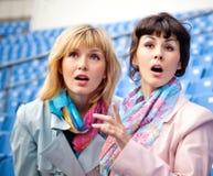 Dos ventiladores de las mujeres que miran la competición Imagen de archivo libre de regalías