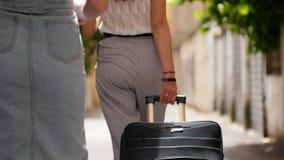 Dos viajero - mujeres felices jovenes con la maleta que va al callejón de la ciudad italiana metrajes