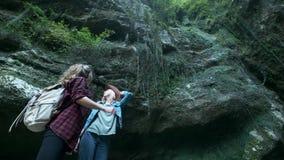 Dos viajeros femeninos caucásicos jovenes viajan a lo largo de una cueva tropical En la mochila que marcha de la parte posterior  metrajes