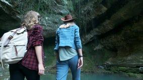 Dos viajeros femeninos caucásicos jovenes viajan a lo largo de una cueva tropical En la mochila que marcha de la parte posterior  almacen de metraje de vídeo