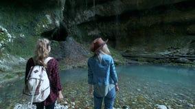 Dos viajeros femeninos caucásicos jovenes viajan a lo largo de una cueva tropical En la mochila que marcha de la parte posterior  almacen de video