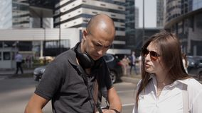 Dos viajeros, hombre y mujer, cambian la batería en una cámara de la acción en el centro de ciudad almacen de metraje de vídeo