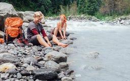 Dos viajeros que restauran en la orilla de la montaña Fotos de archivo libres de regalías