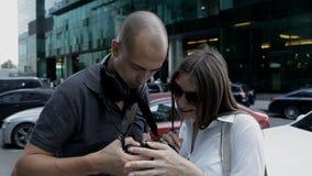 Dos viajeros un hombre y una mujer están viendo las fotos capturadas en la situación de la cámara en el centro de ciudad entre metrajes
