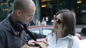 Dos viajeros un hombre y una mujer están viendo las fotos capturadas en la situación de la cámara en el centro de ciudad entre almacen de video