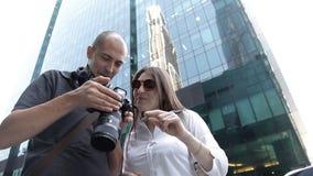 Dos viajeros un hombre y una mujer están viendo las fotos capturadas en la situación de la cámara en el centro de ciudad entre almacen de metraje de vídeo