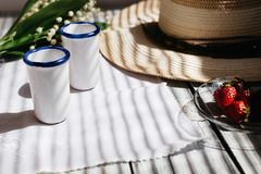 dos vidrios blancos de la porcelana, un sombrero, ramo del lirio de los valles, fresas en una tabla de madera, luz del sol imagen de archivo