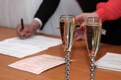 Dos vidrios con champán en el fondo de la fabricación del novio Fotos de archivo