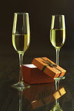Dos vidrios con champán o el vino blanco y la caja de regalo en la tabla del espejo Composición de las celebridades Foco selectiv Imagen de archivo libre de regalías