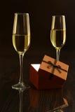 Dos vidrios con champán o el vino blanco y la caja de regalo en la tabla del espejo Composición de las celebridades Foco selectiv Imágenes de archivo libres de regalías