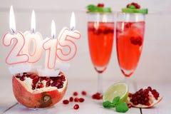 Dos vidrios con el champán y las velas rojos 2015 Foto de archivo