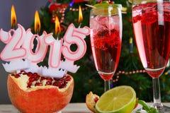 Dos vidrios con el champán y las velas rojos 2015 Imagen de archivo libre de regalías