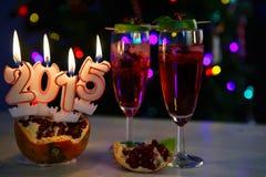 Dos vidrios con el champán y las velas rojos 2015 Fotografía de archivo